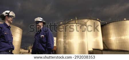 oil and fuel workers with giant storage tanks, sunset in late evening - stock photo