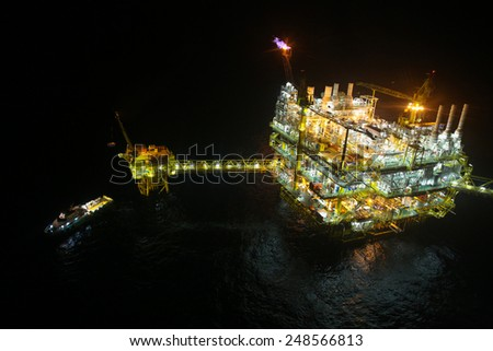 oil and gas construction in night view. View from helicopter night flight. Oil and gas platform in offshore - stock photo