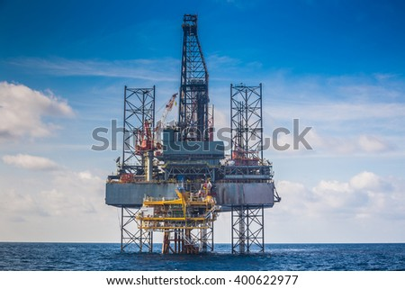 Oil and gas drilling rig work over remote wellhead platform to completion oil and gas produce well. - stock photo