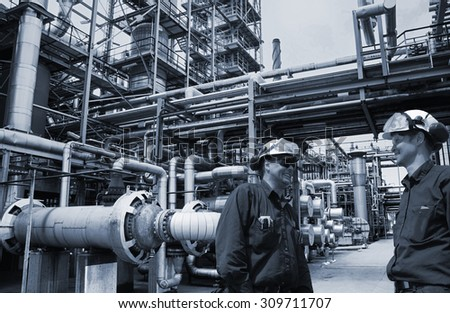 oil and gas engineers inside large petrochemical refinery, blue metal toning concept - stock photo