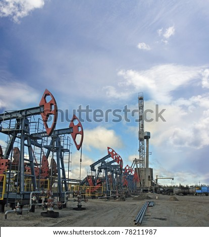 Oil and gas industry. Work of oil pump jack and rig on a oil field. - stock photo