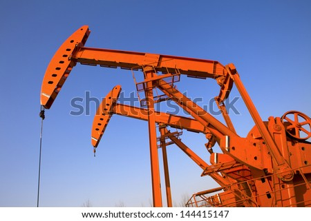 Oil and gas industry. Work of oil pump jack on a field. - stock photo