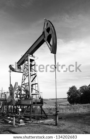 Oil and gas industry. Work of oil pump jack on a oil field. Black and white photo - stock photo