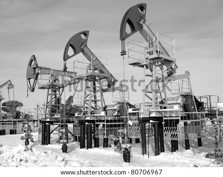 Oil and gas industry. Work of oil pump jack on a oil field.. Black and white photo - stock photo