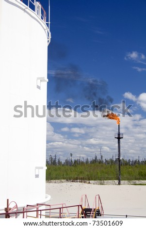 Oil and gas industry. Work of oil pump jack on a oil field.. Burning of gas on a petrochemical plant - stock photo