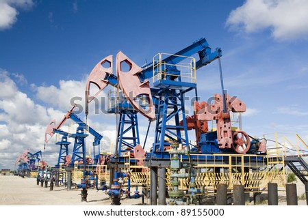 Oil and gas industry. Work of oil pump jack on a oil field in desert - stock photo