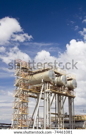 Oil and gas industry. Work of refinery petrochemical plant. Oil reservoir and storage tank of mineral oil. Blue sky above oil field - stock photo