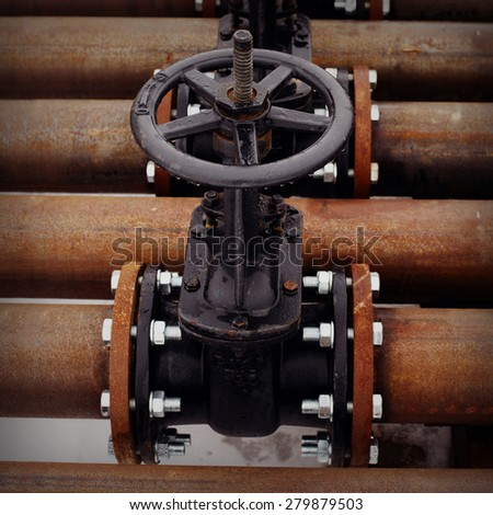 Oil and gas pipeline valves on a rusty piping - stock photo