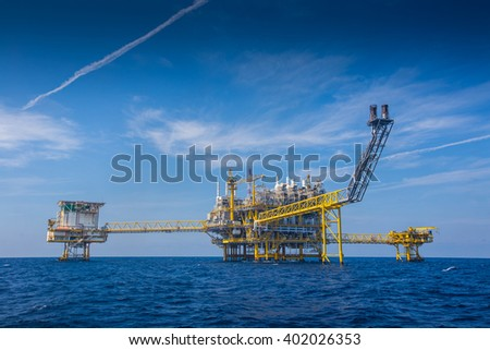 Oil and gas processing platform at center, wellhead platform at right, flare platform in front of processing platform and accommodation platform at left. - stock photo