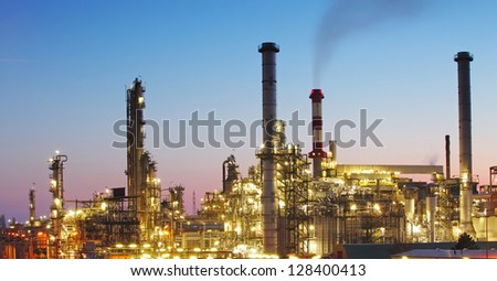 Oil and gas refinery at twilight with reflection - factory - petrochemical plant - stock photo