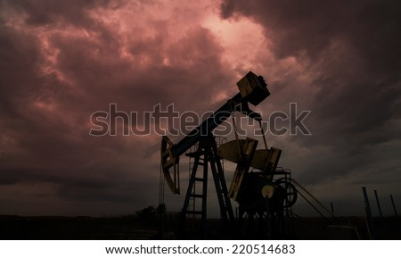 Oil and gas well silhouette in remote rural area, profiled on dramatic warm sky - stock photo
