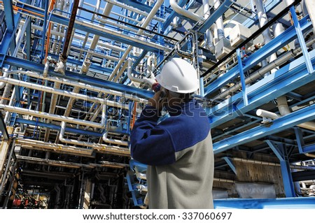oil and gas worker inside large pipelines constructions inside refinery industry - stock photo