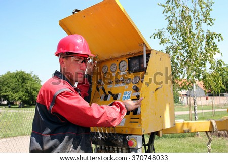 Oil and Gas Worker. Oil and gas well drilling worker operates drilling rig machinery. Oil and Gas Industry. Selective focus. - stock photo
