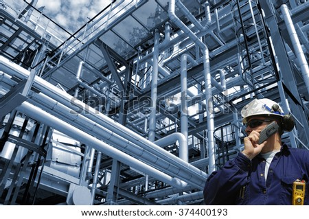 oil and gas worker, pipelines and refinery, blue toning background - stock photo