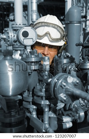 oil and gas worker with main pipelines machinery, slight blue metal toning surrounding the worker - stock photo