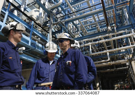 oil and gas workers inside large pipelines constructions, chemical refinery industry - stock photo
