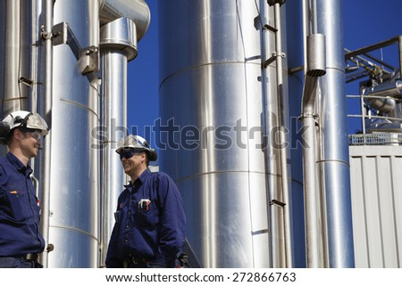 oil and gas workers with giant giant gas-pipes, pipelines in background - stock photo