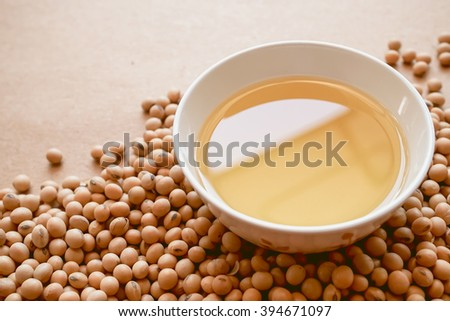 oil and soy beans on brown paper - stock photo