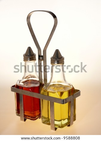 Oil and vinegar bottles in a wire rack on white background. - stock photo