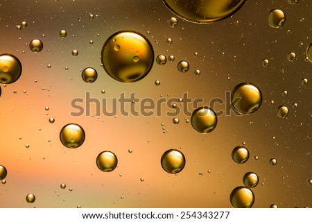 Oil and water abstract in gold and brown with a rainbow effect - stock photo