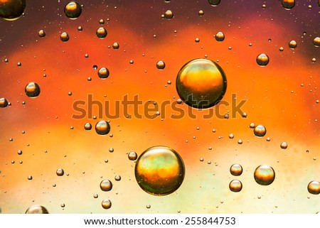 Oil and water abstract in yellow, orange, red and gold - stock photo