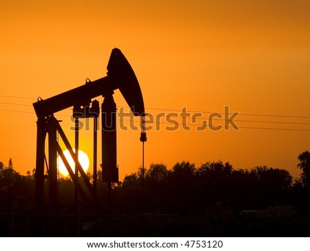 Oil Derrick at sunset. - stock photo