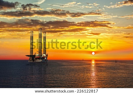 Oil drilling rig in sunset time. - stock photo