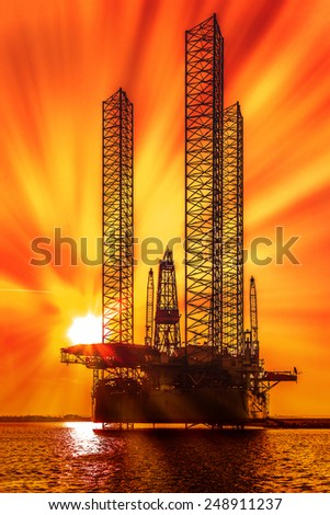 Oil drilling rig in sunset time at sea. - stock photo