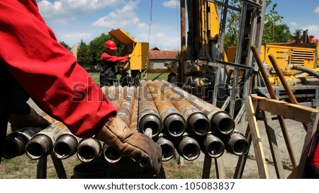 Oil drilling rig workers lifting drill pipe.  Oil and Gas Industry. Drilling Rig.  Oil and Gas Worker. - stock photo