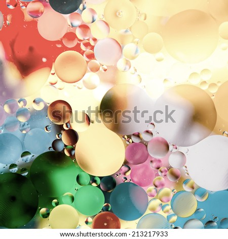 Oil drops in water on a coloured background - stock photo
