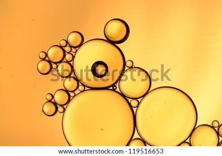 oil drops on the water surface in orange - stock photo