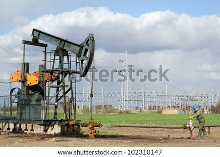 oil field with pumpjack and oil worker - stock photo