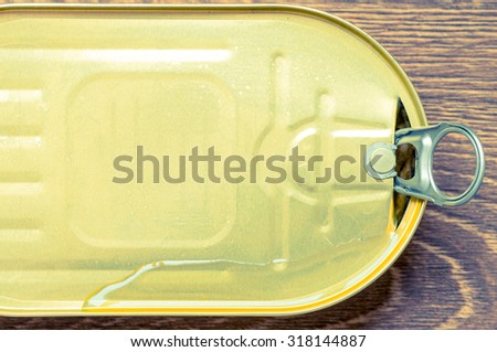 Oil flows through the lid of a tin can top view - stock photo
