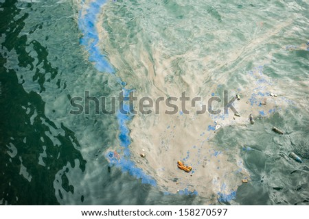 oil fuel spilling water pollution - stock photo