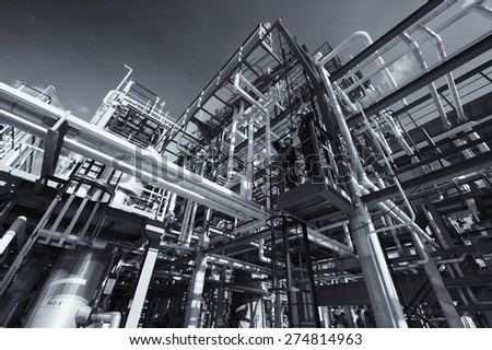 oil, gas and fuel pipelines inside refinery, two oil-workers standing above on landing, silver toning. - stock photo