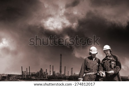oil gas, fuel and industrial pollution, two workers in foreground, toning concept - stock photo