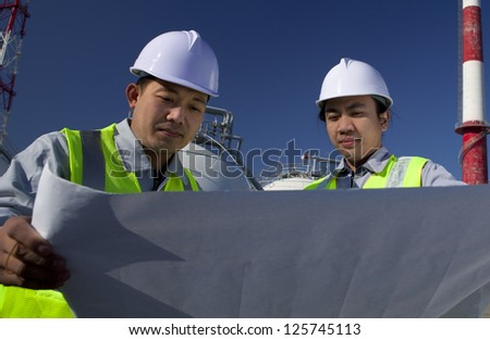 oil gas industrial engineer checking plan with storage tank and tower refinery on the background - stock photo