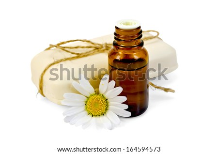 Oil in a bottle, a bar of white soap, tied with twine, daisy flower isolated on white background - stock photo