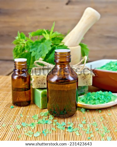 Oil in two bottles, two bars of homemade soap, bath salt, nettle in a mortar on a wooden boards background - stock photo