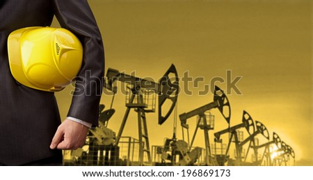 Oil Industry Pump jack with one oil worker in an orange vest with hand holding yellow helmet  torso and hand engineer yellow hardhat for security  No face Unrecognizable person - stock photo