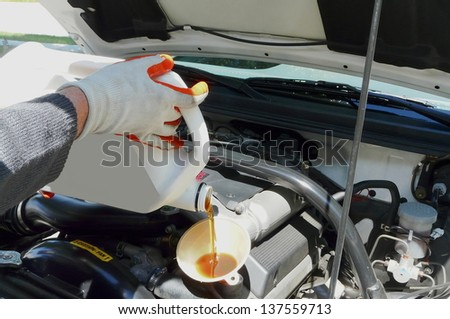 Oil is being added with a funnel from the left side of a car. Man is wearing nitrile dipped work gloves. - stock photo