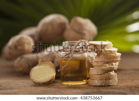 Oil of ginger in a small glass bottle macro and root on tropical leaves background - stock photo