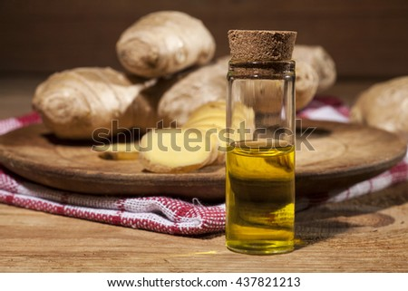 Oil of ginger in a small glass bottle macro and root on wooden table - stock photo