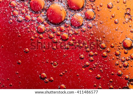 Oil on water illuminated background with orange and red backdrop lighting. Many bubble edges and details in this psychedelic image. - stock photo