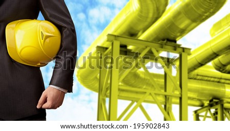 oil or gas refinery, turning on and off pipeline valve on blue sky  background torso and hand engineer yellow holding helmet for workers security construction worker No face Unrecognizable person - stock photo