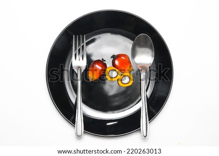 Oil palm fruits on plate - stock photo