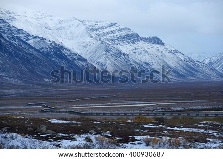 oil pipeline with mountain in northern alaska - stock photo