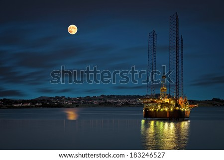 Oil platform at night time and the moon.  - stock photo