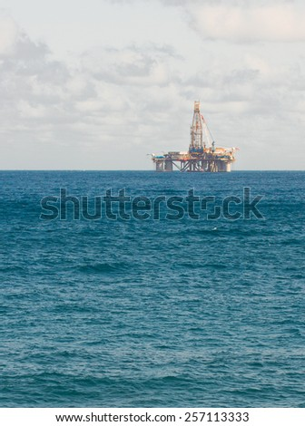 oil platform in blue  sea at day - stock photo