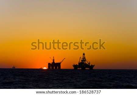 Oil platform silhouette in gulf of mexico - stock photo